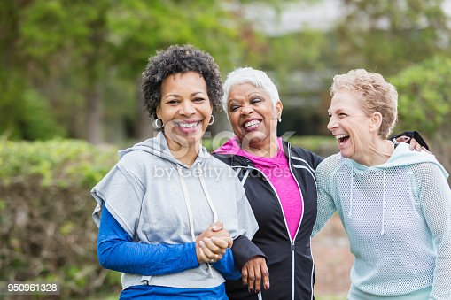 Three multi-ethnic women wearing hooded sweatshirts, hanging out together in the city, laughing while they take a walk. The woman with black hair, looking at the camera, is in her 50s and her senior friends are in their 60s.