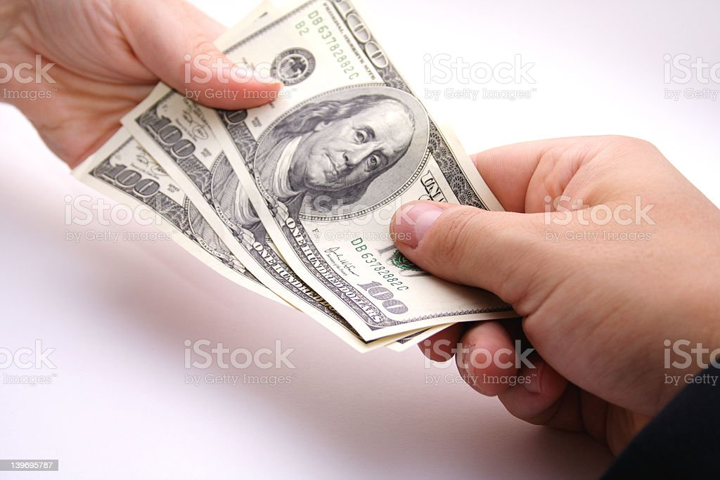 Three one hundred dollar bills exchanging hands royalty-free stock photo