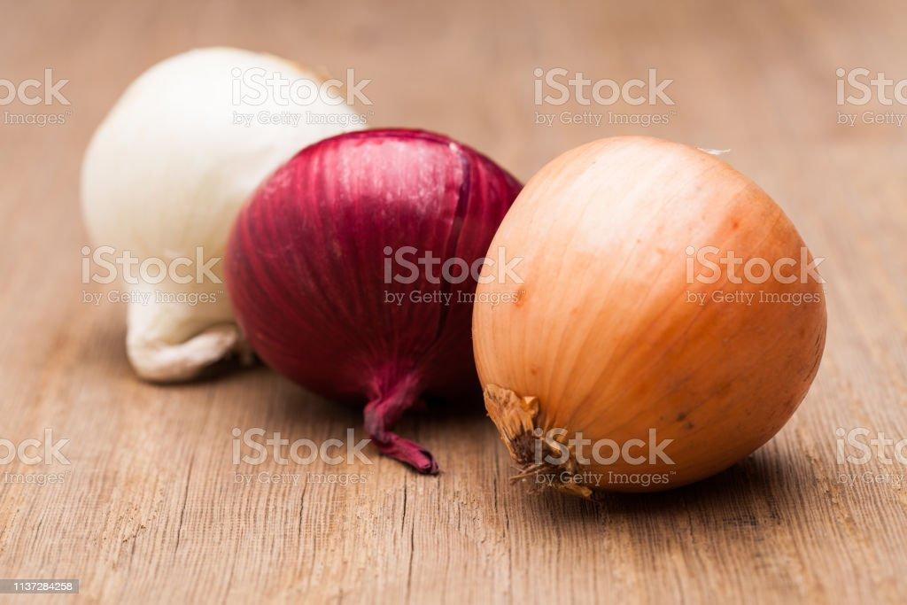 木桌上的三個洋蔥 - 免版稅一組物體圖庫照片