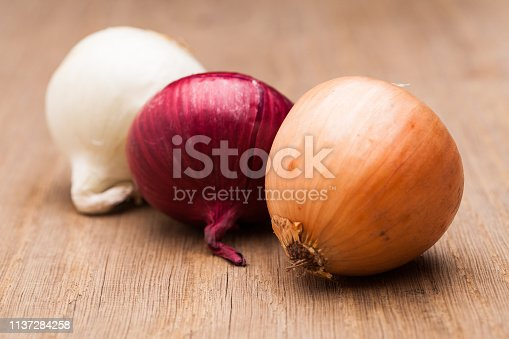 Three onions on wooden table