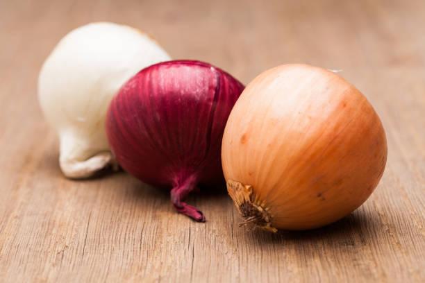 Drei Zwiebeln auf Holztisch – Foto