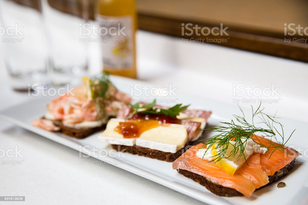 Three open sandwiches on a white plate​​​ foto