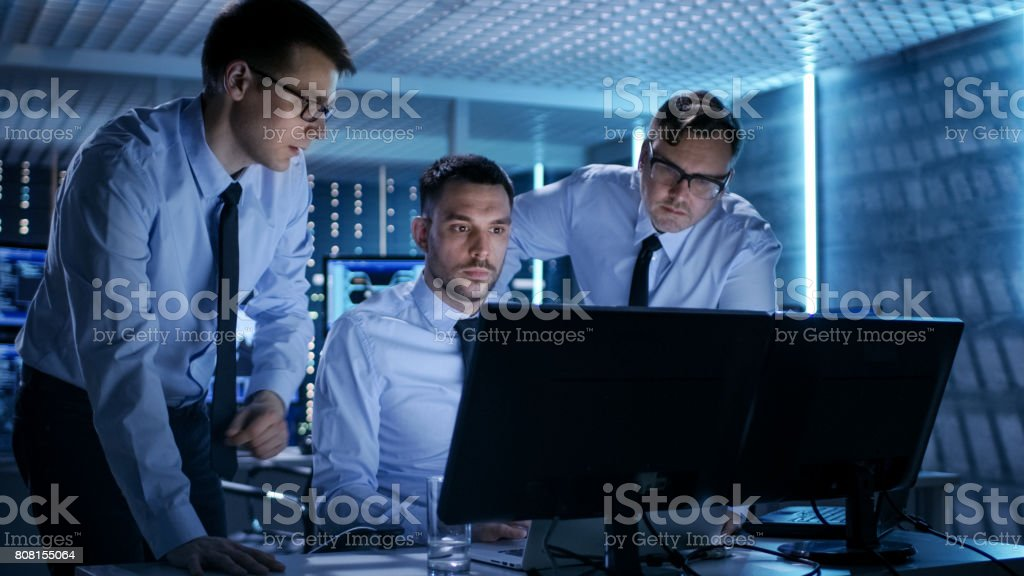 Three Operations Engineers Solving Problem in a Monitoring Room. In System Control Room Multitple Displays Show Various Data. stock photo