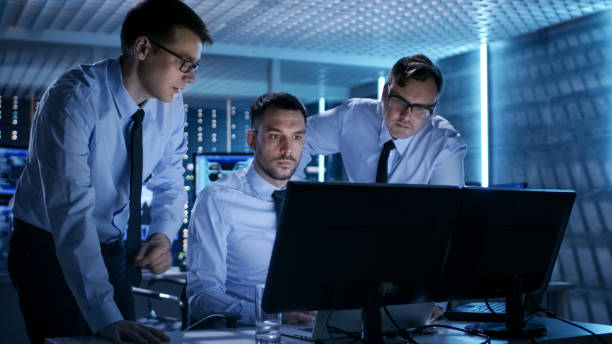 Três operações engenheiros resolvendo o problema em uma sala de monitoramento. Em monitores de Multitple de sala de controle sistema mostre vários dados. - foto de acervo