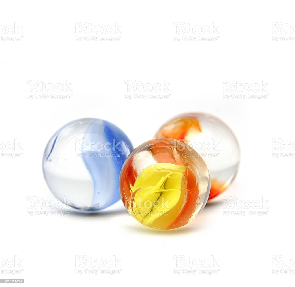 Three orange, blue and yellow glass marbles on white surface stock photo