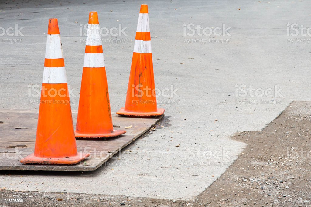 Three orange cones are lined up on a metal plate that is covering...