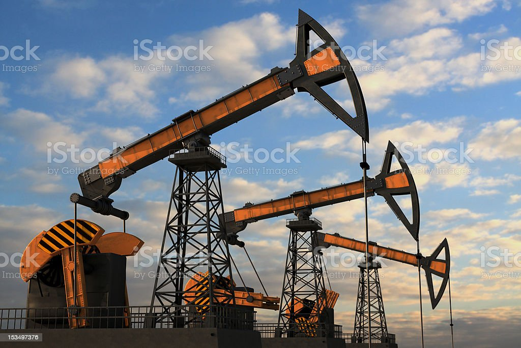 Three orange oil pumps against cloudy sky royalty-free stock photo