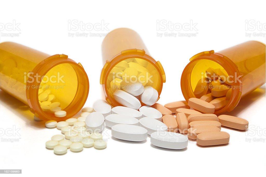 Three orange prescription bottles spilling different pills stock photo