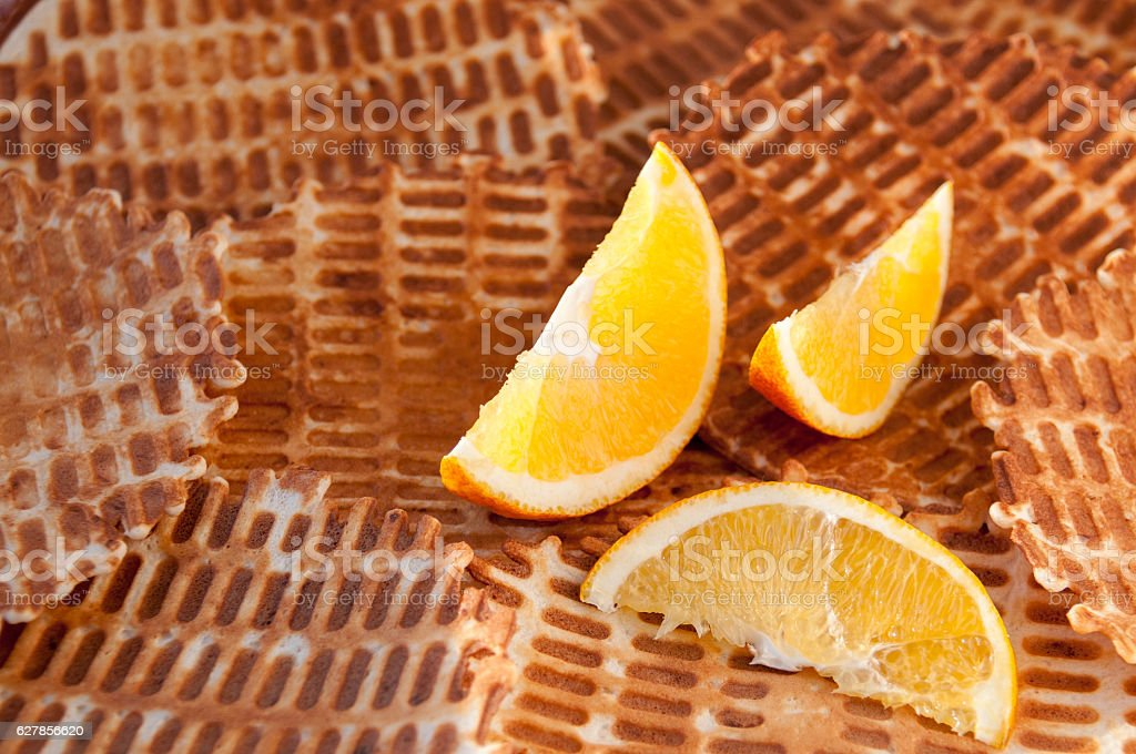 Three orange slices on the background of home wafers stock photo