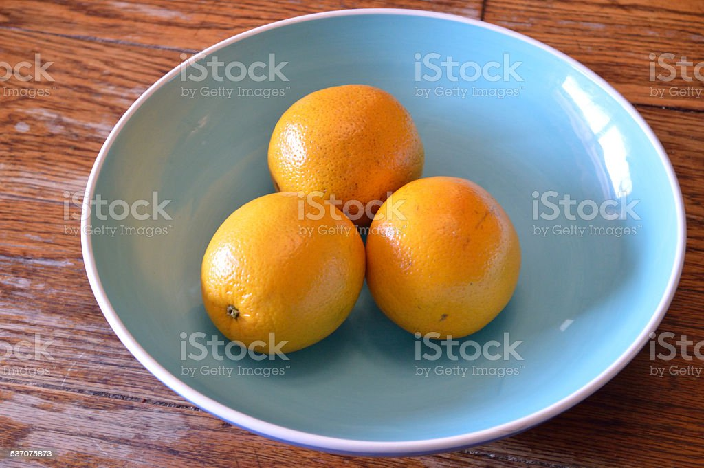 Three Oranges in Blue Bowl stock photo