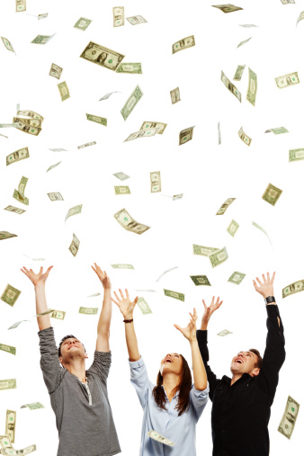 Three smiling young adults with arms raised try to catch the many dollars raining down on them. Isolated on white.