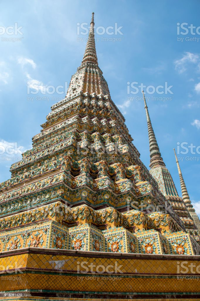 Three Pagoda are in Wat Pho that was named as the temple of the pagoda or chedi that are decorated with yellow glaze or glazed tiles or dark blue. stock photo