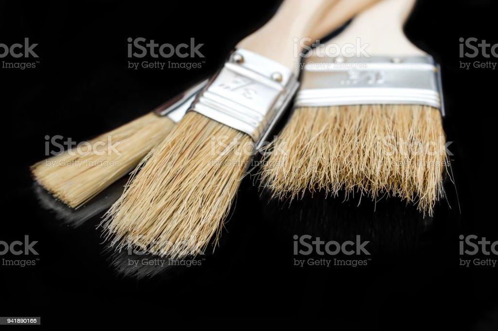 Three Paint Brushes On Black Reflective Background Stock