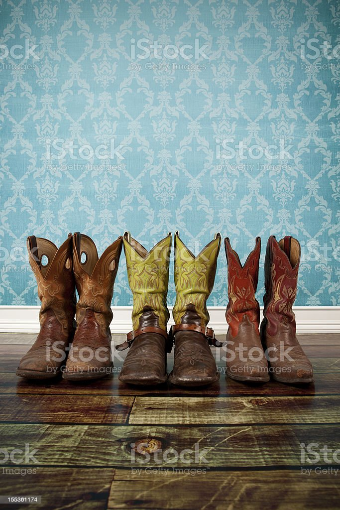Three pair of cowboy boots on wood flooring with blue wall stock photo