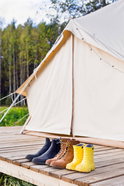 Three pair of shoes near bell tent stock photo