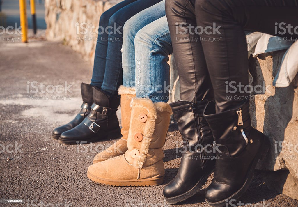 Three pairs of girls legs with boots on them stock photo
