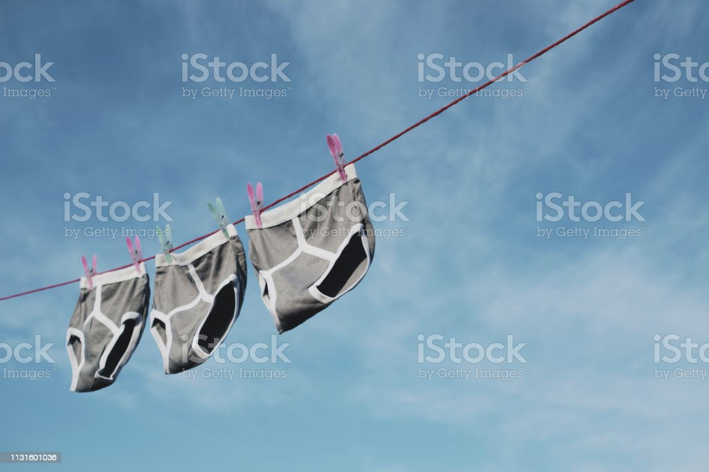 Three pairs of Grey retro Y-Front underpants on a washing line against a blue sky. stock photo