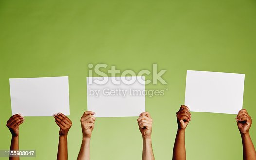 Six hands comprising three pairs hold  three blank pieces of paper up against a green background.