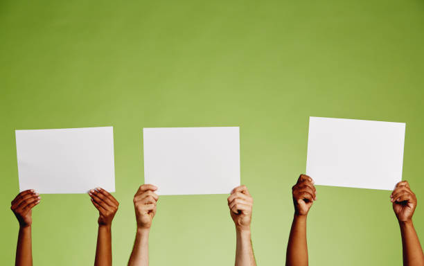Three pairs of hands hold up blank sheets of paper stock photo