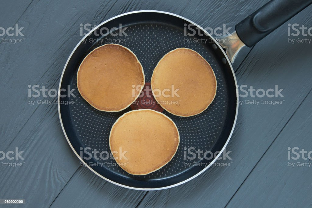 Three pancakes in a frying pan on wooden surface stock photo