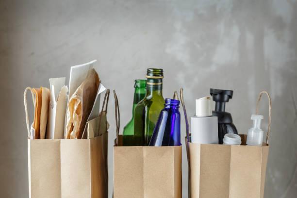 trois sacs en papier avec les déchets ménagers triés - séparation photos et images de collection