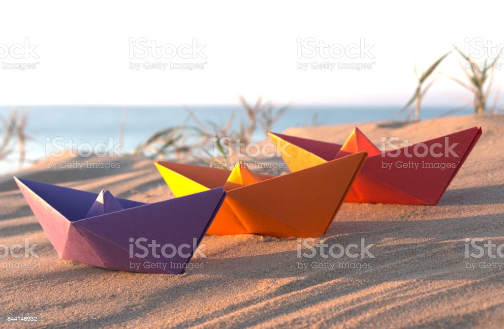 Three paper boats on a beach: Purple, orange and red stock photo