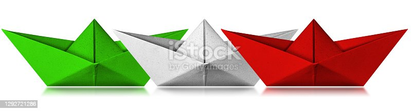 Three paper boats with the colors of the Italian flag, green, white and red. Isolated on white background with reflections, photography.