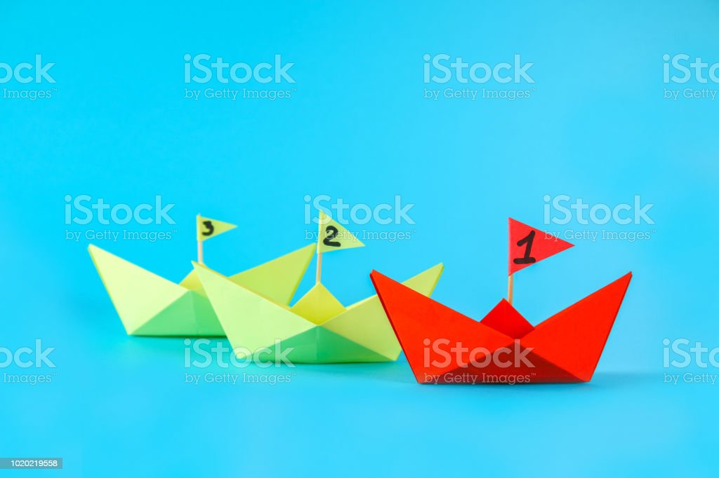 Three paper ships compete who swims faster. Red wins the ship