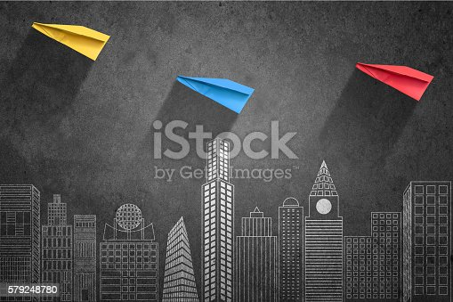 Multi colored papers airplane flying over cityscape.