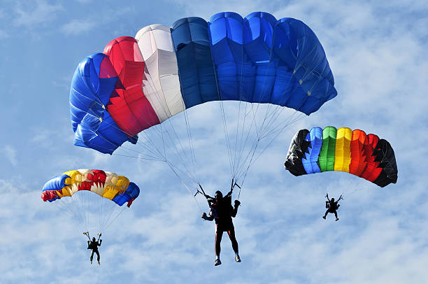 Three parachutes three colorful parachutes on blue sky. parachuting stock pictures, royalty-free photos & images
