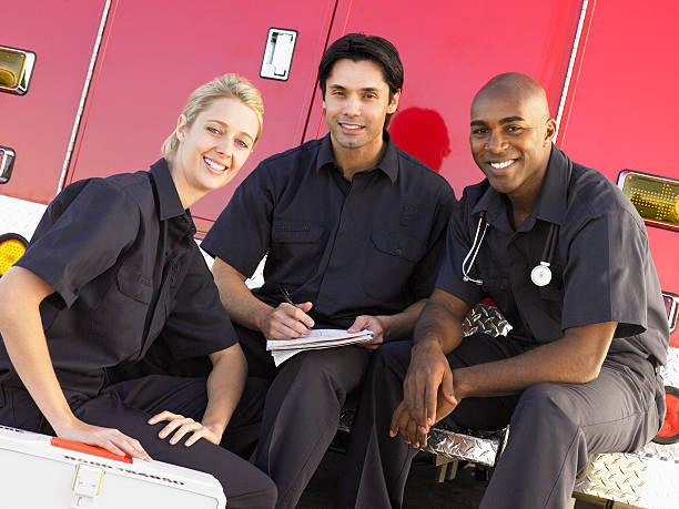 trois auxiliaires médicaux par leur ambulance - auxiliaire médical photos et images de collection