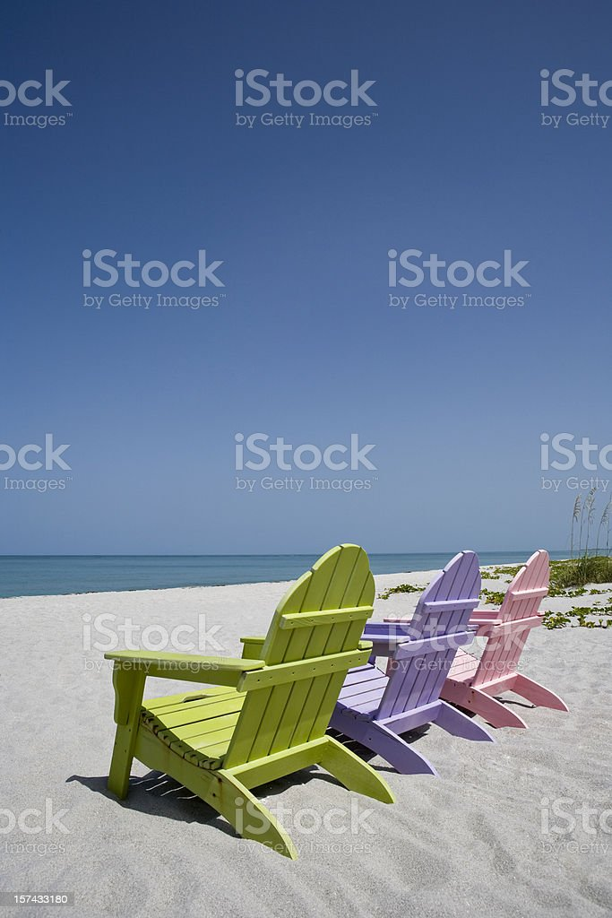Three pastel colored beach chairs on sand at beach stock photo