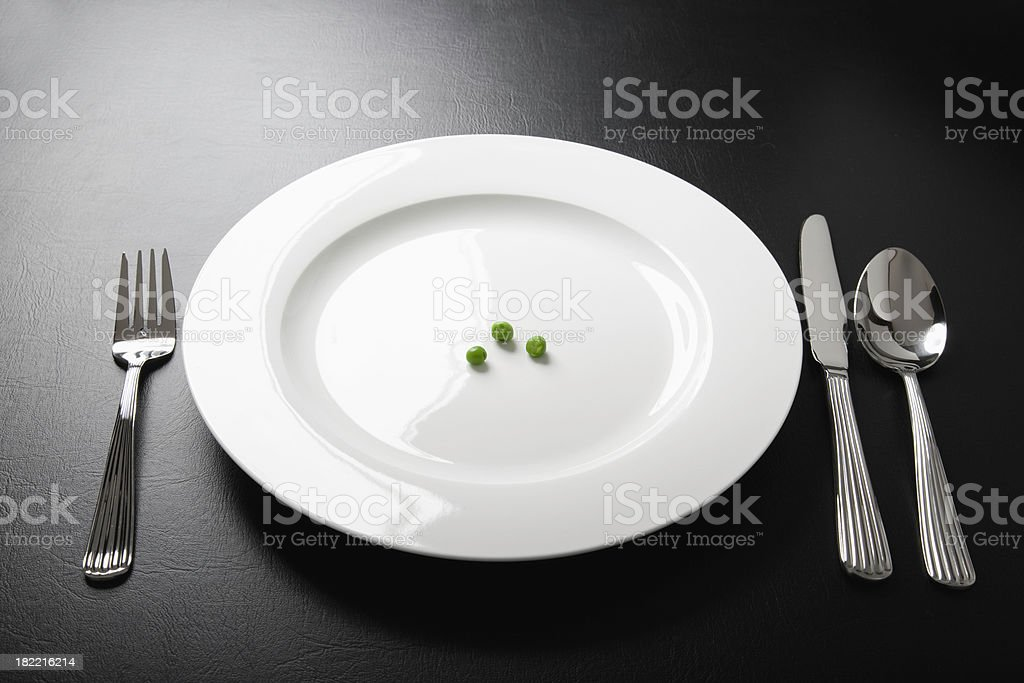 Three peas on a white plate - dieting concept royalty-free stock photo