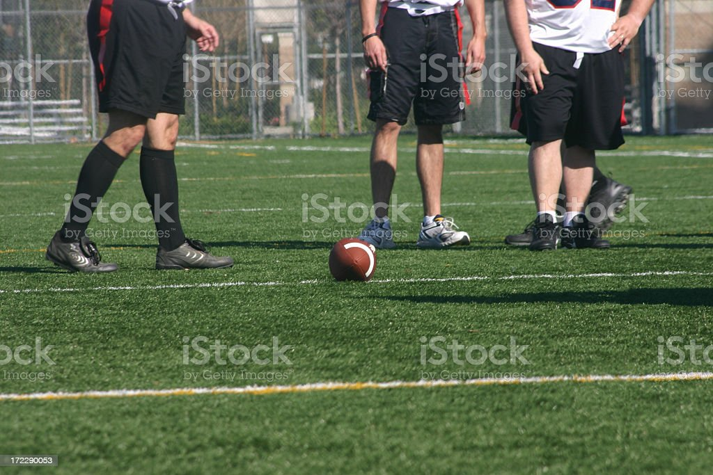 Three people and a football on a field royalty-free stock photo