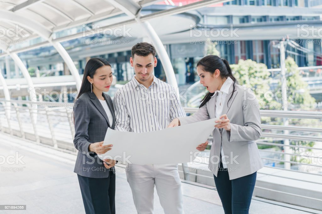 Three people are business manager and engineer meeting project at three people are business manager and engineer meeting project at construction site man holding blueprint malvernweather Images
