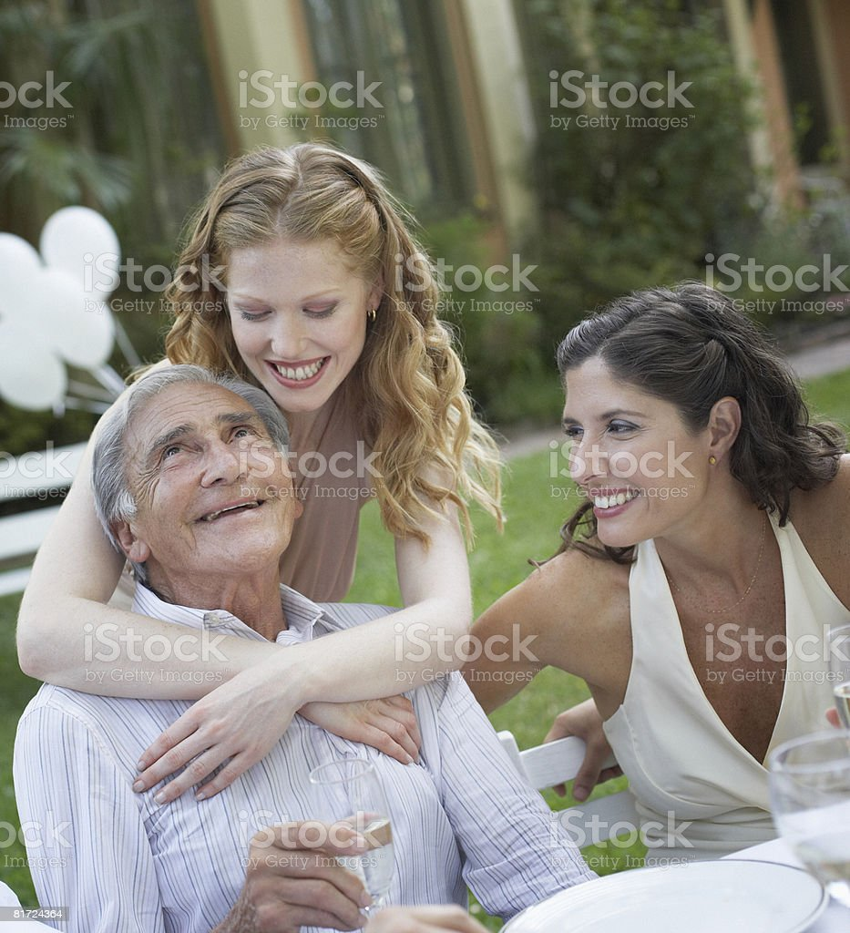 Three people at outdoor party smiling and being affectionate royalty-free stock photo