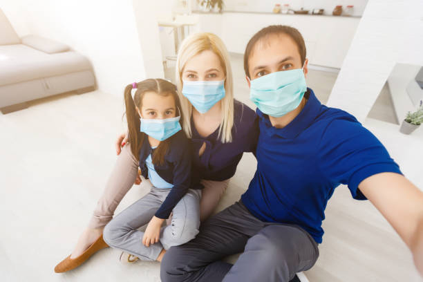 Three people Caucasian family with dad, mom and daughter staying at home wearing facial masks, portrait stock photo