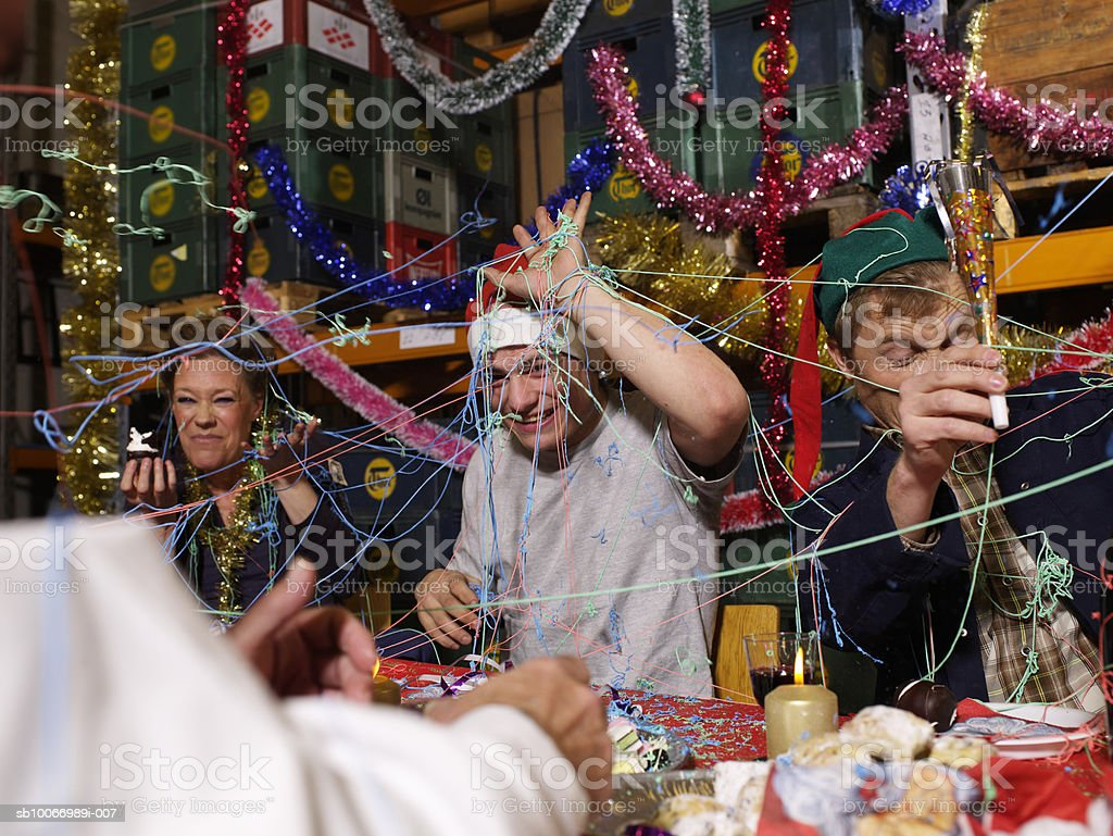 Three people covered in party streamers laughing at charismas table in warehouse royalty free stockfoto