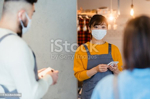 Three people are covering their faces with protective face masks and having a staff meeting in a café before reopening.