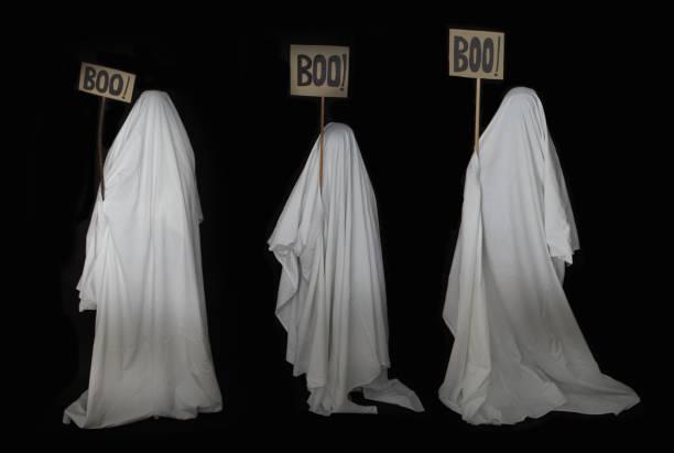 drei menschen getarnt als geister mit einem weißen blatt - geist kostüm stock-fotos und bilder