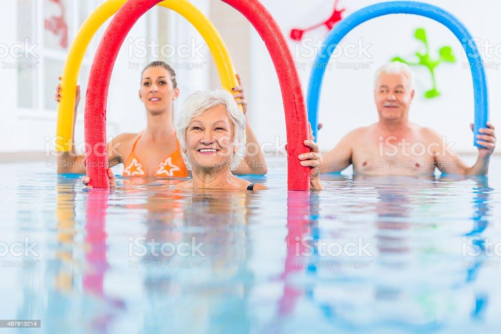 Three people doing aquarobics in a swimming pool stock photo