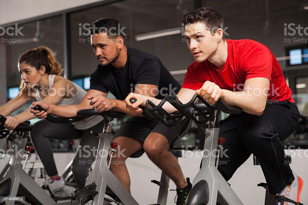 Three people doing cardio on a bicycle stock photo