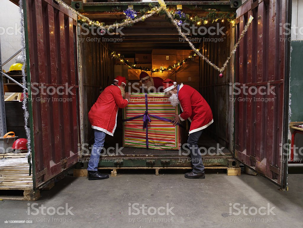 Three people dressed in santa clothes lifting present from cargo container in warehouse 免版稅 stock photo
