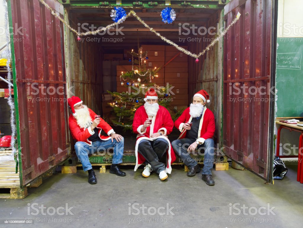 Three people dressed in santa clothes sitting in cargo container holding plastic wine cups royalty-free stock photo