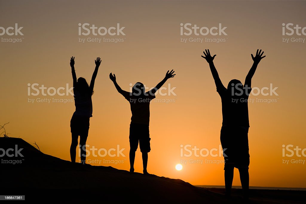 Three people enjoying the sunset while raising arms stock photo