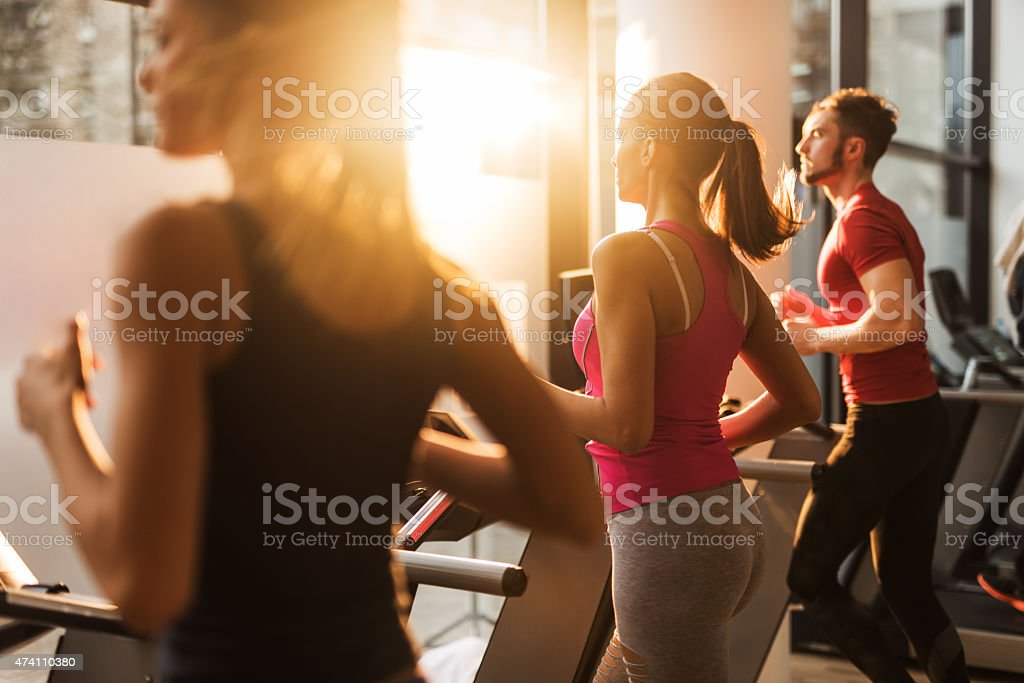Three people exercising on treadmills in a gym. stock photo