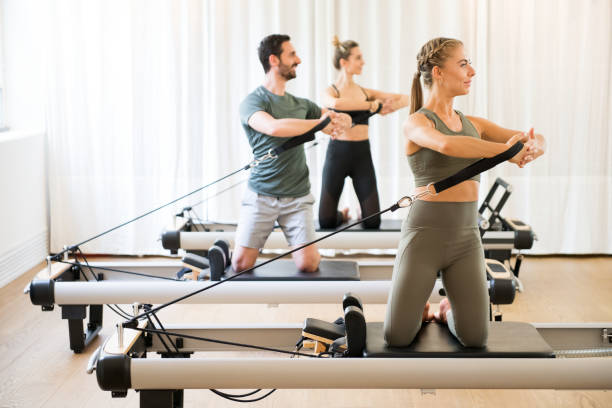 three people exercising torson rotation at gym - metodo pilates foto e immagini stock
