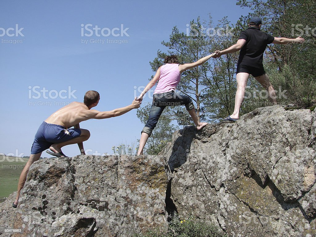 Three people helping each other climb royalty-free stock photo