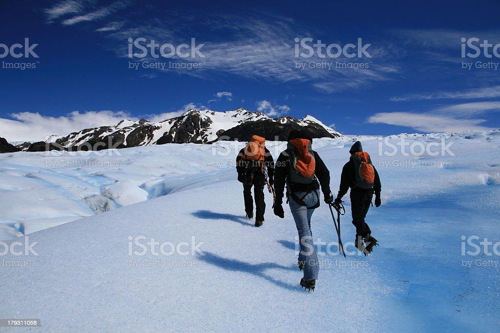 Three people hiking on a snowy glacier stock photo
