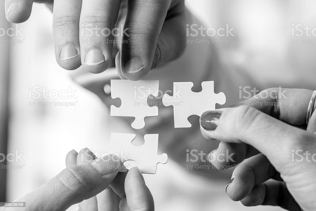 Three people holding puzzle pieces to match them stock photo